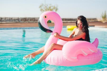 プールでの膨脹可能なマットレスのフラミンゴに座っている日焼け少女