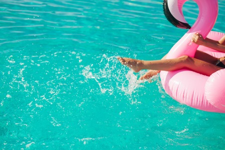Tan Mädchen sitzt auf aufblasbaren Matratze Flamingos im Pool Standard-Bild