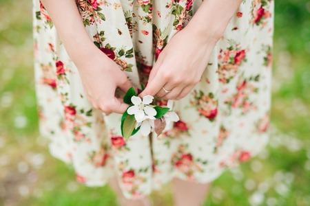 girl in flower dress holding sakura or cherry blossom in hands