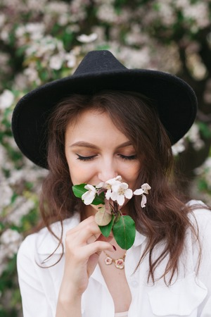 Girl sniffing cherry flowers in park at spring