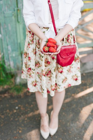 woman in flower dress holding a bunch of strawberries.