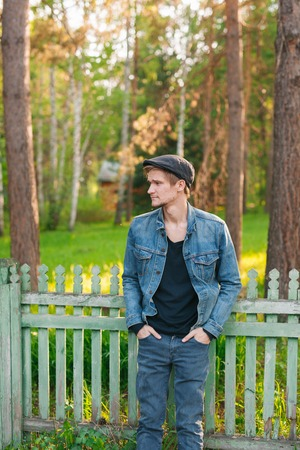 southern european descent: Retro-styled young man. He is leaning on a fence. Stock Photo