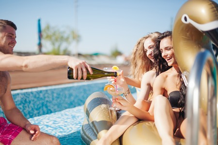 20s: Group Of Friends Having Party In Pool Drinking Champagne. 20s. Stock Photo