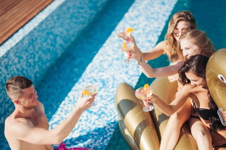 Group Of Friends Having Party In Pool Drinking Champagne. 20s. Stock Photo