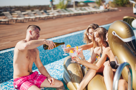 20's: Group Of Friends Having Party In Pool Drinking Champagne. 20s. Stock Photo