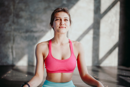 Woman practicing yoga in lotus pose indoor. Fit girl in sportswear sitting in Padmasana exercise, meditation session in the morning at fitness studio, full length Stock Photo