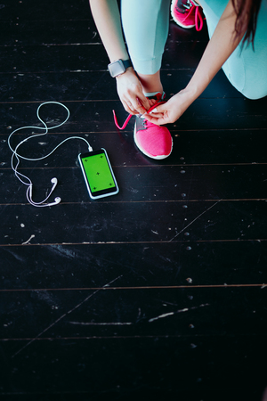 Runner woman tying running shoes laces getting ready for race on run track with smartphone and earphones for music listening on mobile phone. Athlete preparing for cardio training. Feet on ground. Stock Photo