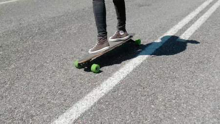 20s female in gray sneakers and black jeans skateboarding on the highway close-up 4k. Stock Photo