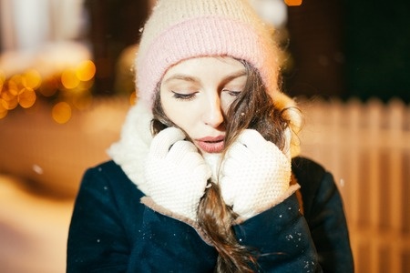Happy winter time in big city of charming girl walking on street in coat with backpack. Enjoying snowfall, expressing positivity, smiling to camera, joyful cheerful mood, true emotions, new year mood