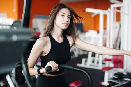 Young beautiful white girl in black sports suit is engaged on a stationary bike in the fitness club.