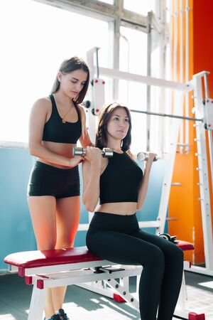 Cute Sporty young woman doing exercise in a fitness center with her personal coach. She is working exercises to strengthen her chest.