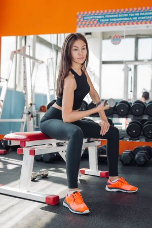 Fit young woman 20s doing shoulder raises with dumbbells in gym 20s Imagens