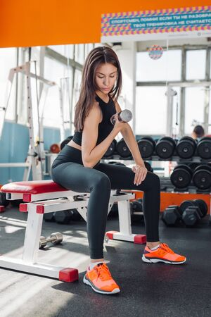 Fit young woman 20s doing shoulder raises with dumbbells in gym 20s Banque d'images