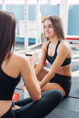 fitness, sport, training, gym and lifestyle concept - two smiling women sitting on the half ball and relaxing after class in the gym