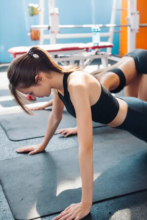 Two woman friends or sportsmen exercising in gym. Imagens