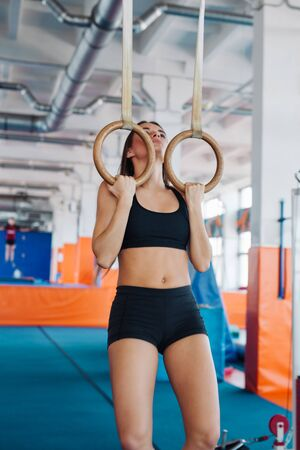 Young fit woman pulling up on gymnastic rings. Muscular woman exercising on gym.