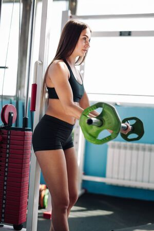 Sportswoman lifting hard barbell at gym interior. Young pretty bodybuilder woman in sportsuit doing workout with bar at gym against the mirror wall Imagens
