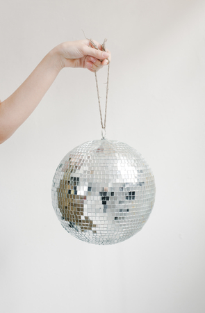 Hand holding disco ball on string isolated on white background.