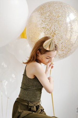 Fashion photo of beautiful woman with balloons. Girl posing. Studio photo.