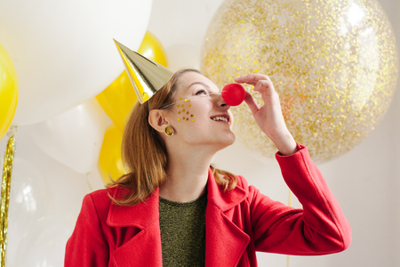 Young woman in a celebratory cap fooling around at a party on the background of falling confetti Stock Photo - 86517616