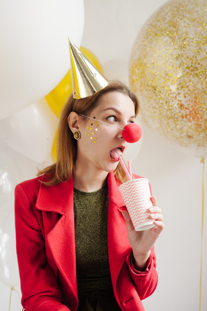Young woman in a celebratory cap fooling around at a party on the background of falling confetti Stock Photo - 86444671