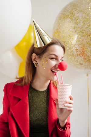 Young woman in a celebratory cap fooling around at a party on the background of falling confetti Stock Photo - 86444672