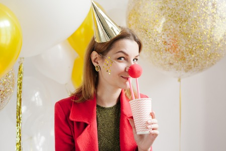 Young woman in a celebratory cap fooling around at a party on the background of falling confetti Stock Photo - 86444674