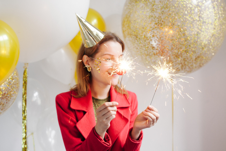 Young woman in a celebratory cap fooling around at a party on the background of falling confetti Stock Photo - 86444675