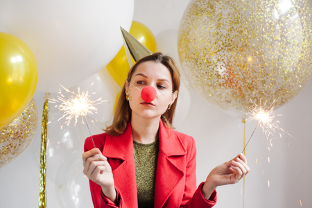 Young woman in a celebratory cap fooling around at a party on the background of falling confetti Stock Photo - 86444676
