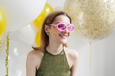 Portrait of happy funny young woman in pink heart shaped glasses.