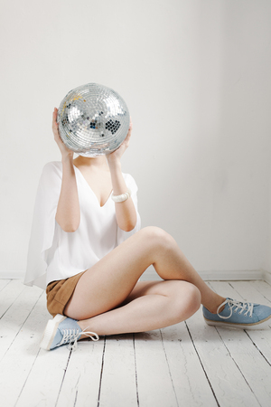 Young hipster woman holding disco ball and posing cheerfully on white background.
