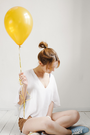 Portrait of cute girl in a studio smiling and playing with yellow balloons, background with copyspace. Imagens