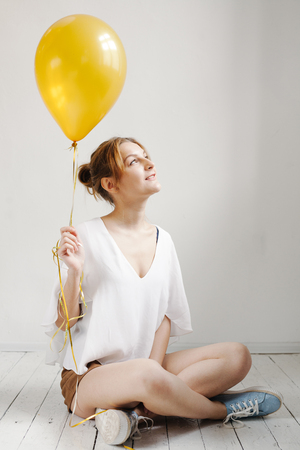 Portrait of cute girl in a studio smiling and playing with yellow balloons, background with copyspace. Фото со стока