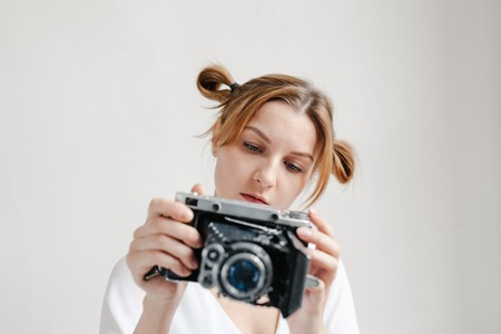 Close up portrait of a smiling pretty girl taking photo on a retro camera isolated over white background.