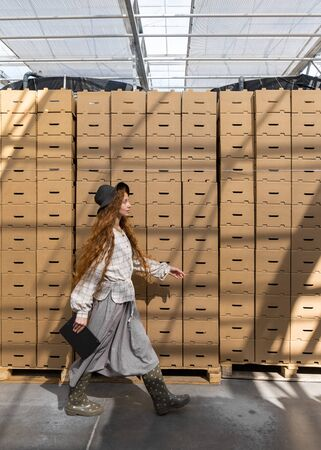 Smiling female worker leaning on boxes. Warehouse interior.