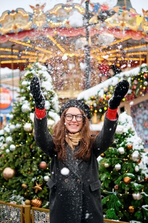 Girl playing with snow in park. young girl throws snow up, a beautiful fair with lights and bulbs, dressed up Christmas trees