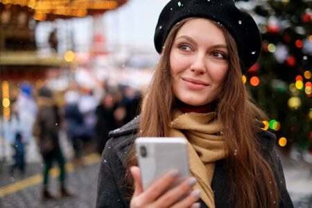 young attractive girl uses a phone on the street, against the background of dressed-up Christmas trees, Christmas mood,