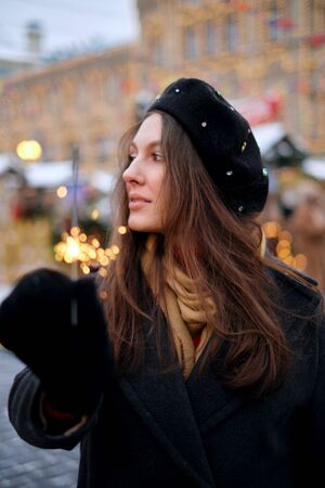 Attractive european lady in beret celebrating new year on the street, holding Bengal light. Outdoor portrait of happy brunette girl posing with sparkler in winter.