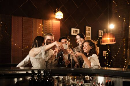 Happy group of friends at the bar having drinks. Imagens