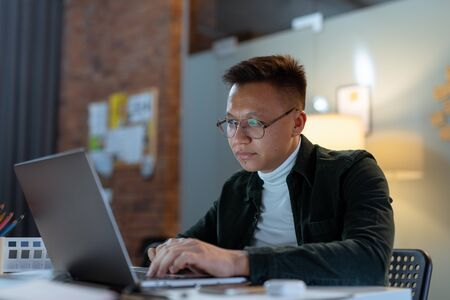 education, deadline and people concept - close up of creative man in glasses working at night office and thinking happy asian freelancer korean man laptop Standard-Bild