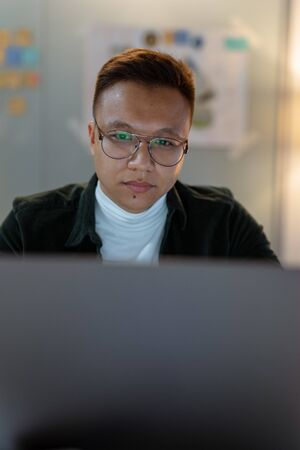 education, deadline and people concept - close up of creative man in glasses working at night office and thinking happy asian freelancer korean man laptop