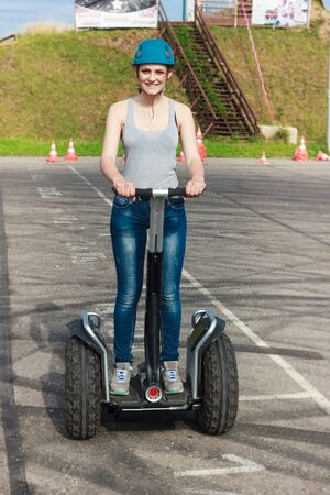 Young lady in a helmet riding on a hover vehicle.