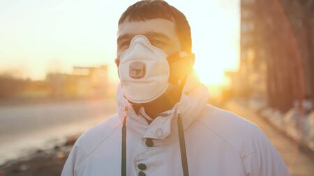 One Man Go Walk outdoor. Corona Virus Flu Mers. Real People N95 Mask. Coronavirus State Emergency. Flatten Curve Covid-19. Social Distancing 2019-ncov. Male outdoor. Sunset or Sunrise sun. City street 写真素材