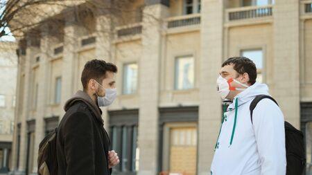 Two Italian Men Talking Public. Pandemic Corona Virus Flu Mers. Real People N95 Mask. Coronavirus State of Emergency. Flatten the Curve Covid-19. Social Distancing 2019-ncov. Male outdoors Italy. 写真素材