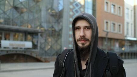 Inscription on build: Clothes and shoes. Real Bearded European Man Portrait. Mustache Human Looking Camera Public. Beard Face. Close-up People Moustache Face. Hood person Portrait. Europe Camera Look.
