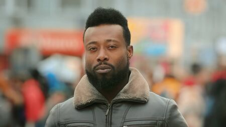 Close up African American man look camera stand street city. Black afro people face portrait closeup. Confident serious. Young adult guy. Urban background. George Floyd. Black lives matter. America.