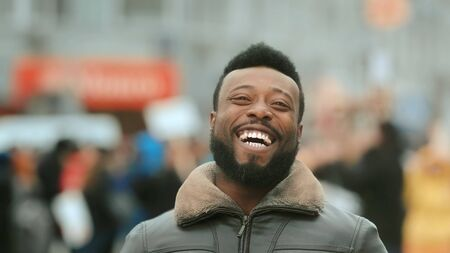 Close-up young adult American black man in jacket smiling and looking at camera. Smile human. Cold winter in New York. Happy african people in city on street closeup look. Male laughing. White teeth. 写真素材