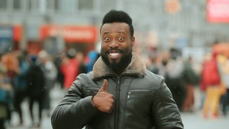 Close-up young adult man show approval gesture. Smile human sign ok. Like recommendation. Cold winter snow. Thumb up. Happy african people in city street finger up closeup. Male laugh symbol victory. 写真素材