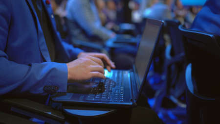 Person type keyboard crowded audience business forum. Viewer seminar listen speaker auditorium. Business man typing notebook political summit. Group people learning education speech in crowd audience