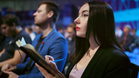 Girl write business note crowded forum audience. Viewer seminar listen speaker auditorium. Business woman writing in notepad financial summit. Group people learning education speech in crowd audience.
